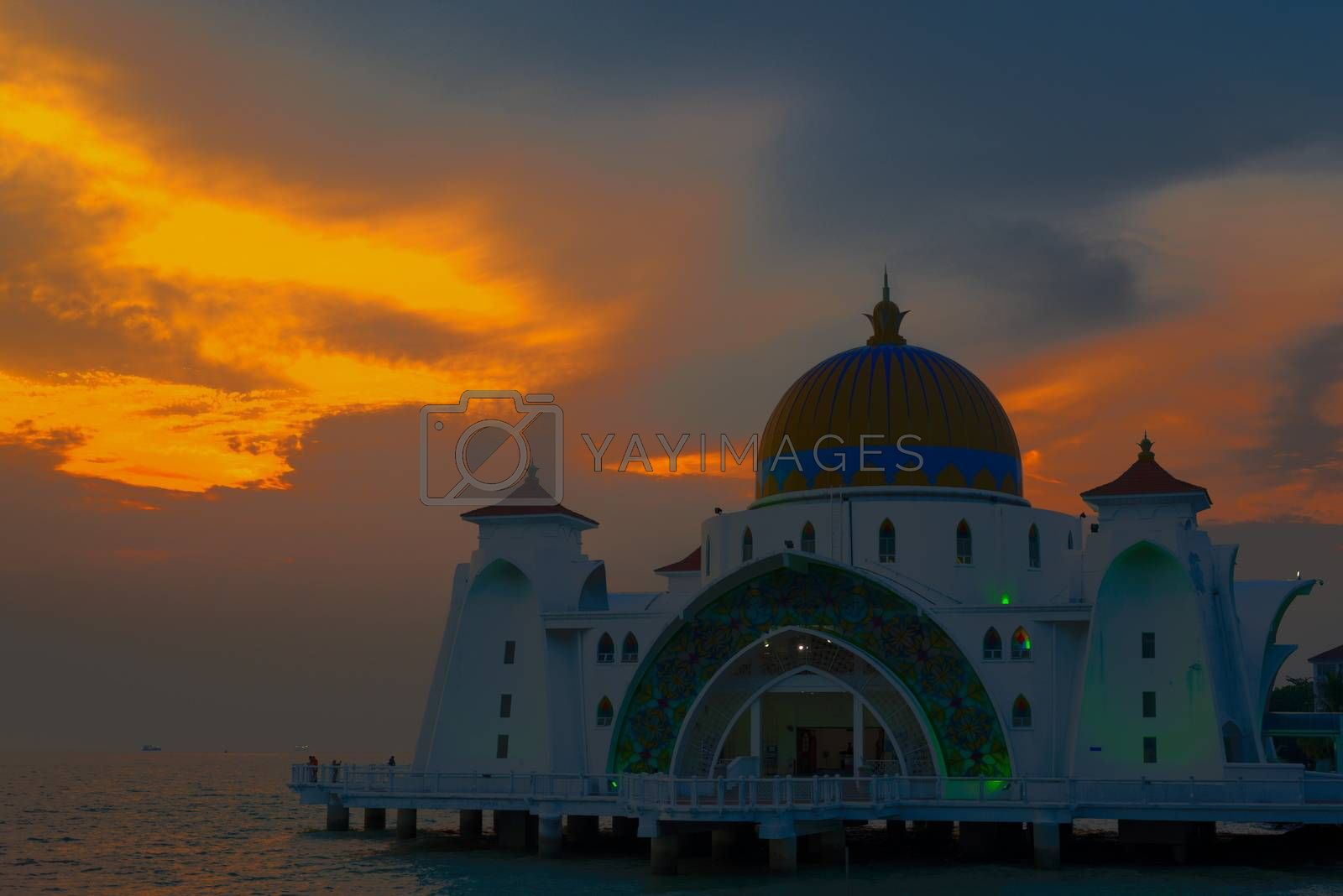 Melaka Straits Mosque at sunset by the water with orange blue grey sky