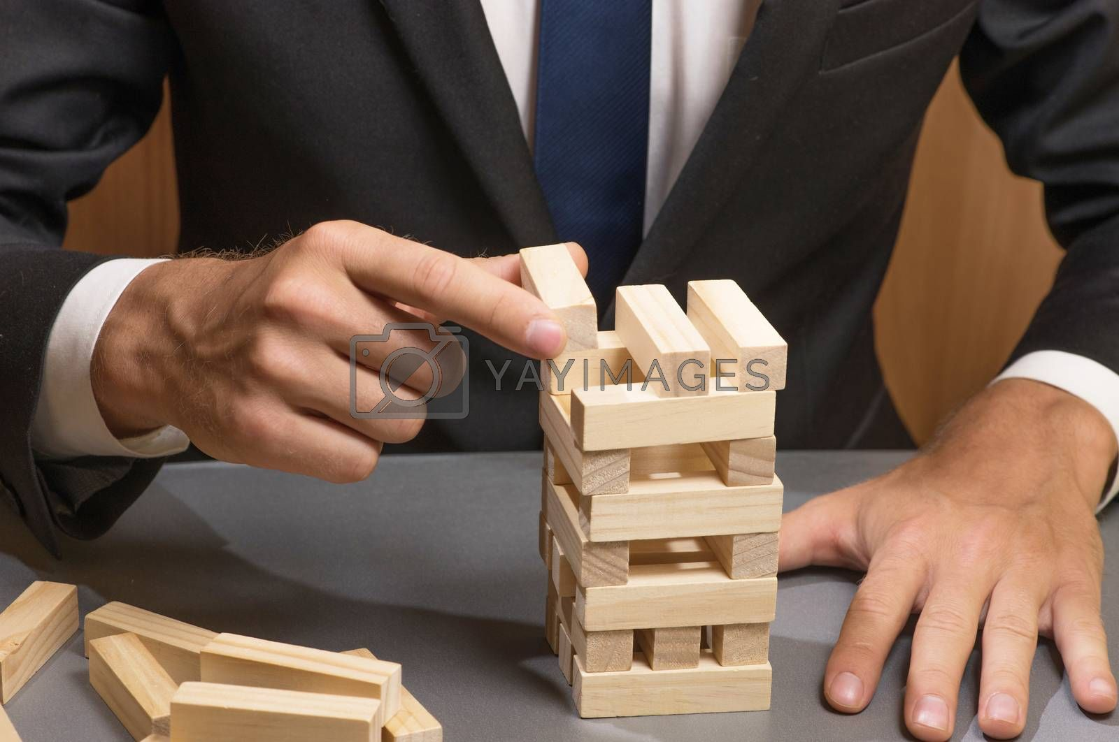 Businessman in business suit building a tower of wooden blocks, strategy and planning in business.