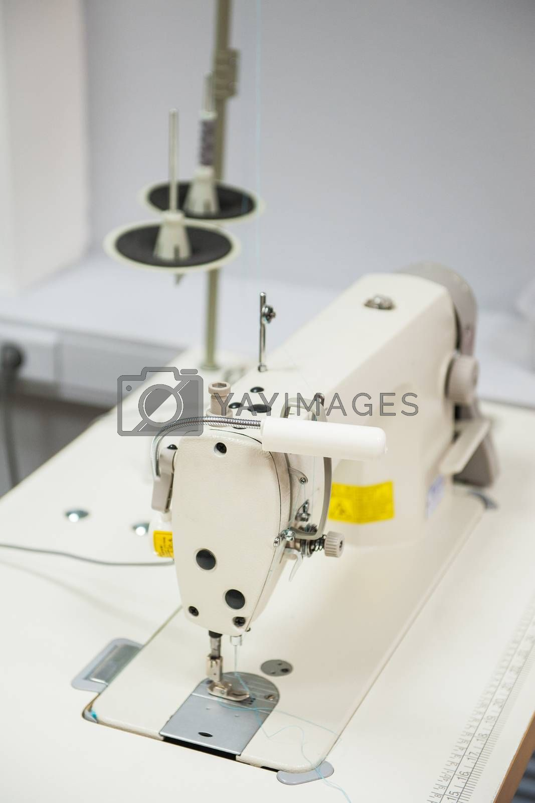 Industrial sewing machine in tailor's workshop