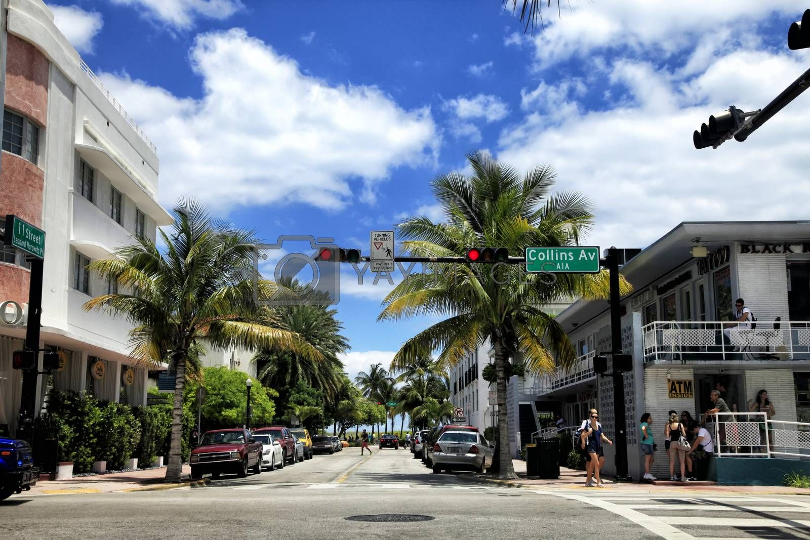 Miami Beach, Florida, USA - May 05, 2013: View along the famous vacation and tourist location on crossing Collins avenue and 11 street in district of South Beach, Miami on a sunny day with cars, palm trees and people visible.