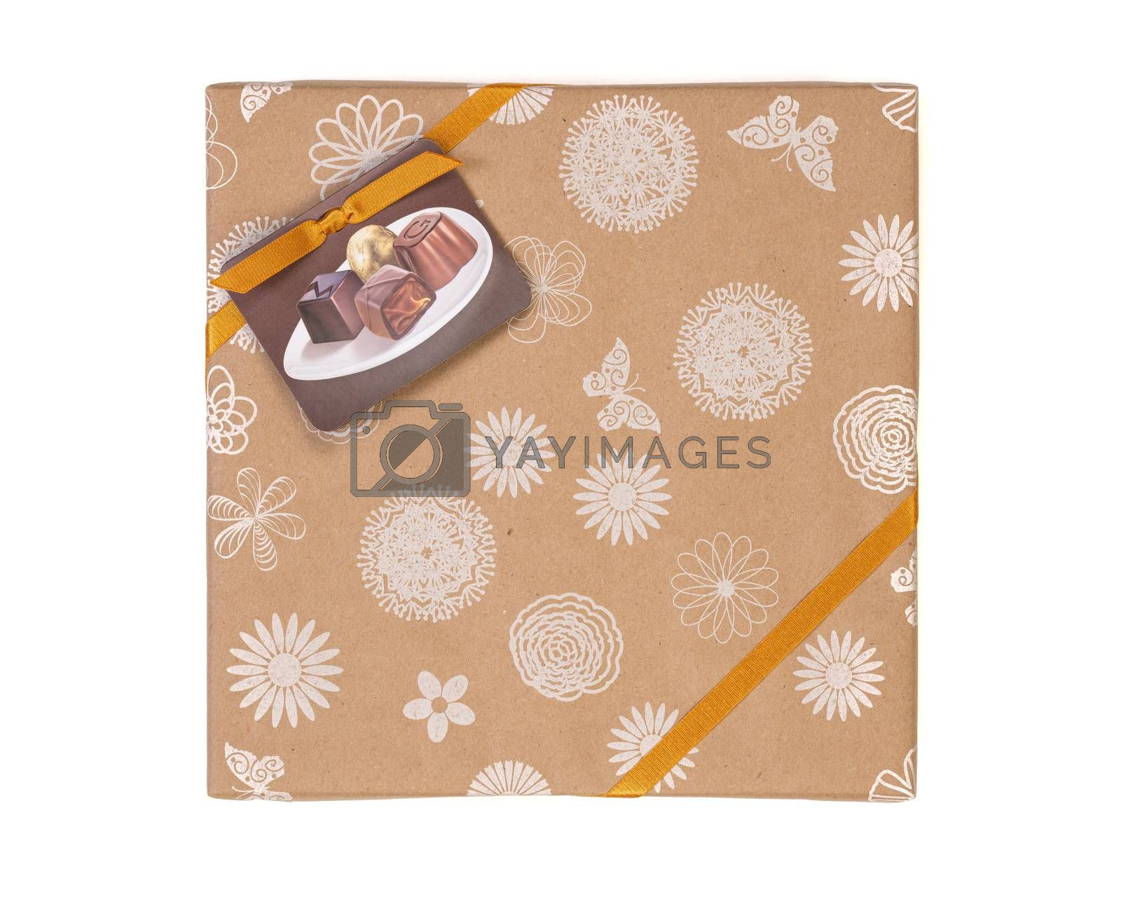 Gift wrapped box with chocolate candies and golden tape on a white background.