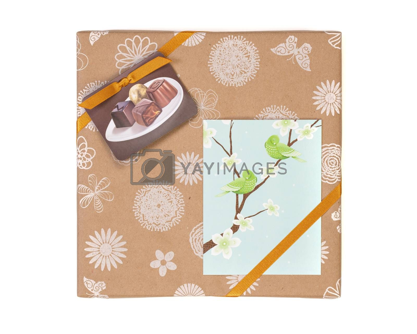 Gift wrapped box with chocolate candies and golden tape on a white background with greeting card.