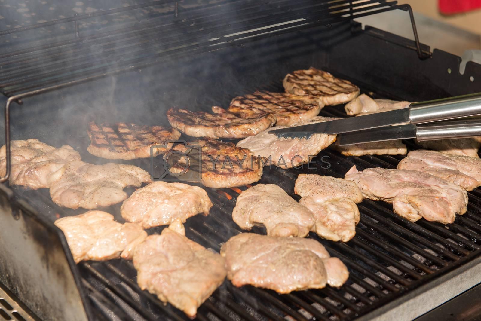 Grilling pork steaks by Dan Totilca