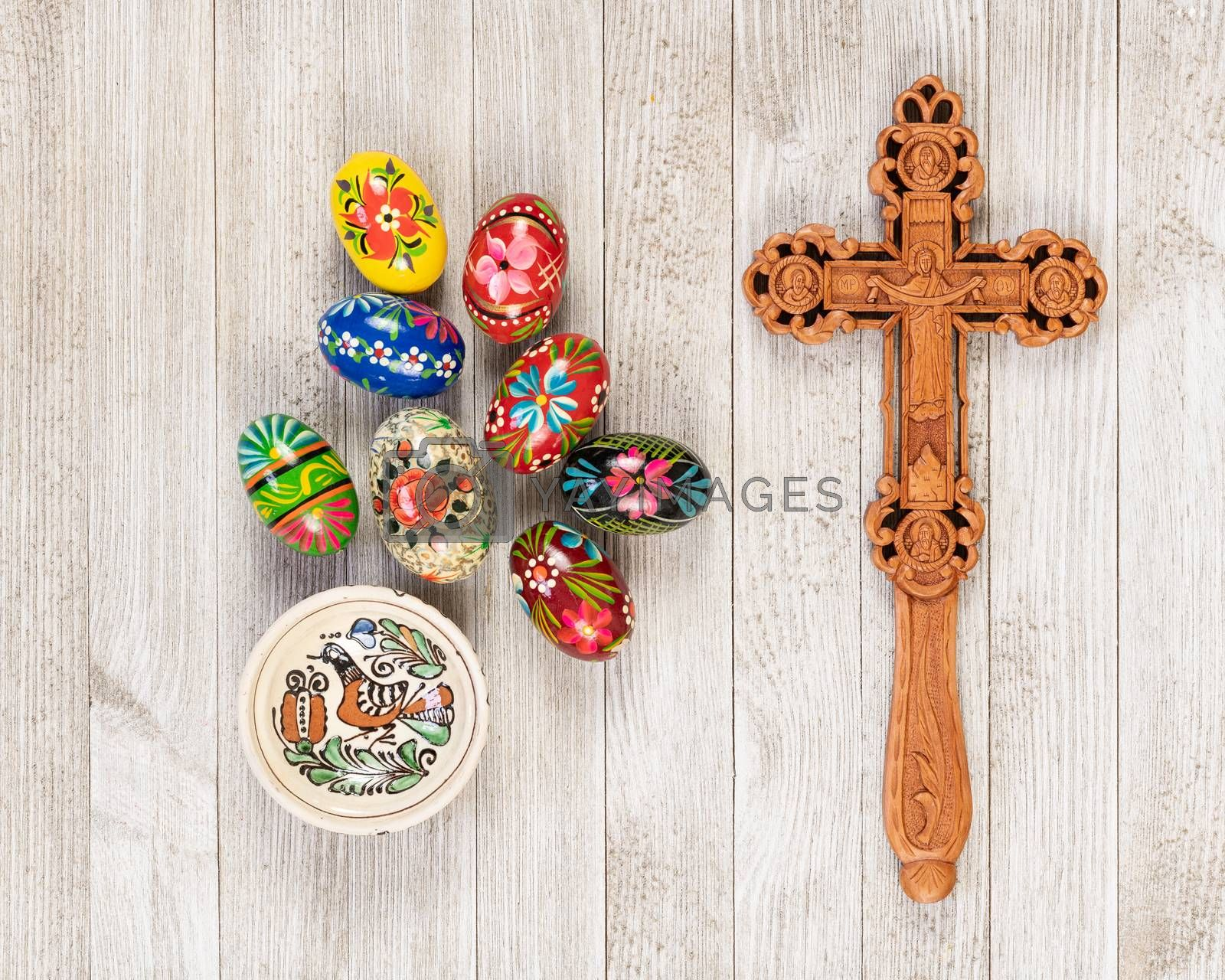 Painted wooden eggs traditional of Eastern Europe with delicately sculpted wooden cross.
