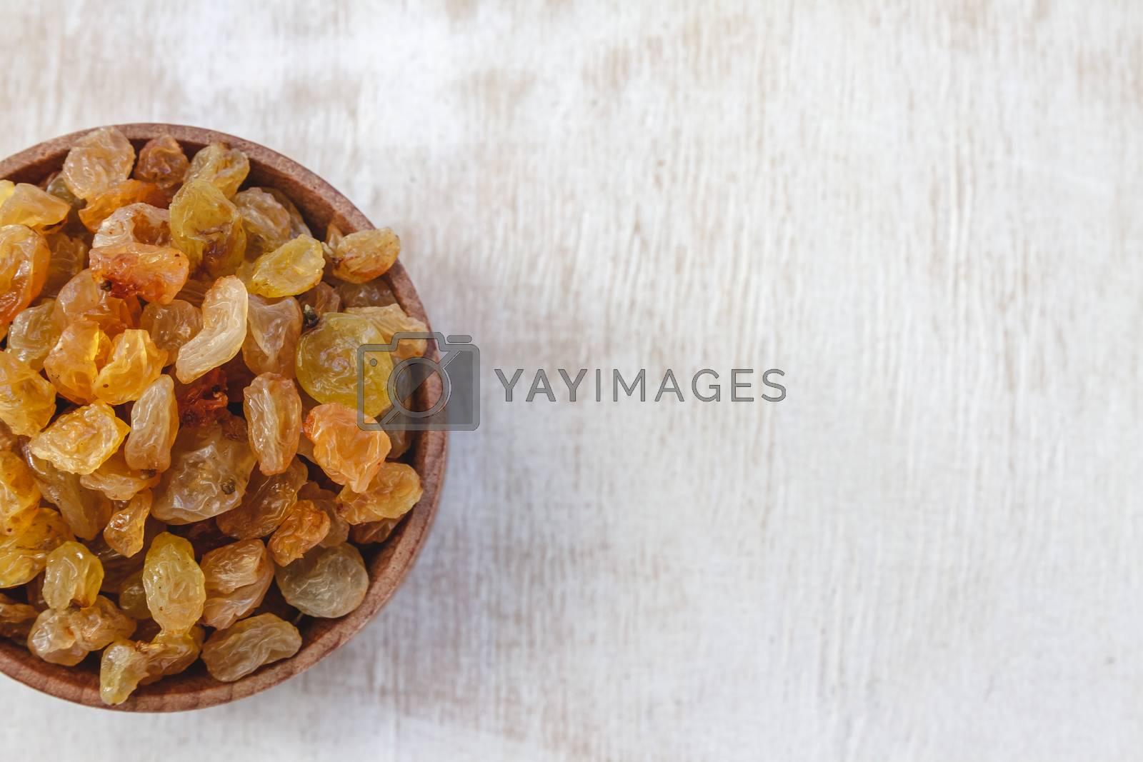 Light yellow raisins in a wooden bowl on a light white backgroun by Tanacha