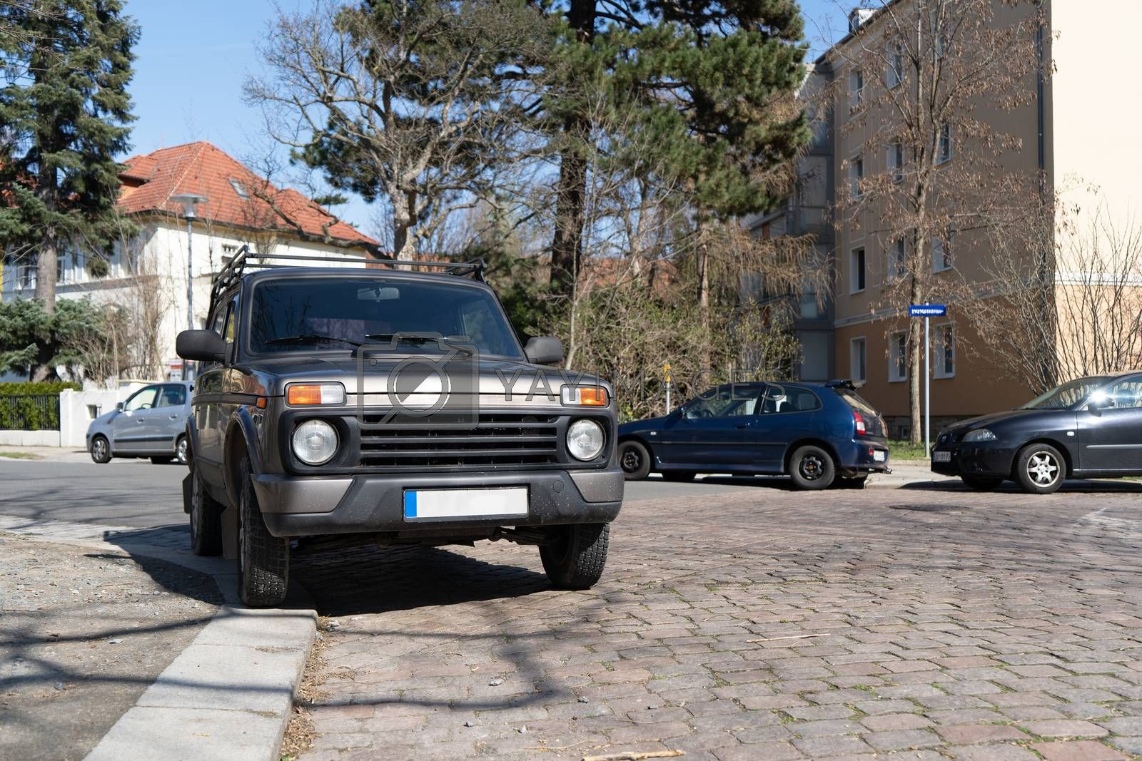 An off-road vehicle is parked on the curb of a German sidewalk. The only mountain such a car can climb in a city.