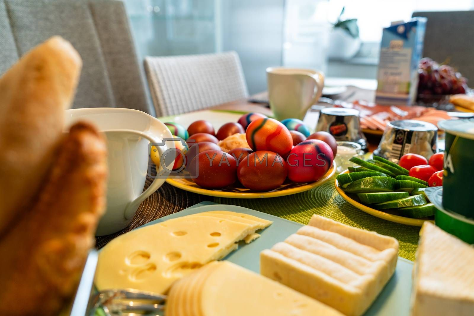 Colored eggs as a traditional symbol of Easter celebration on a breakfast table in Germany together with other toppings.
