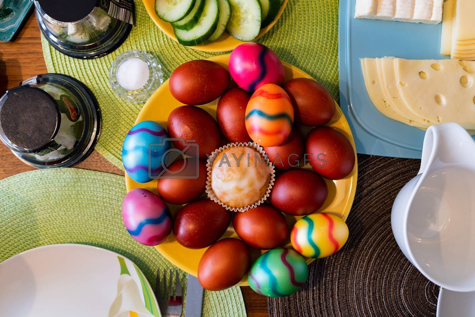 A top view on colored eggs arranged on a plate as a traditional symbol of Easter celebration in Germany together with other toppings.