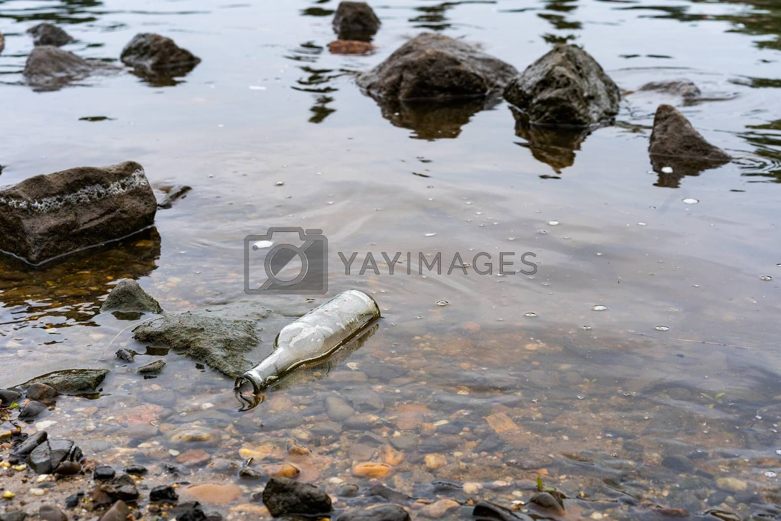 A clear bottle lies in the river as litter polluting the environment.
