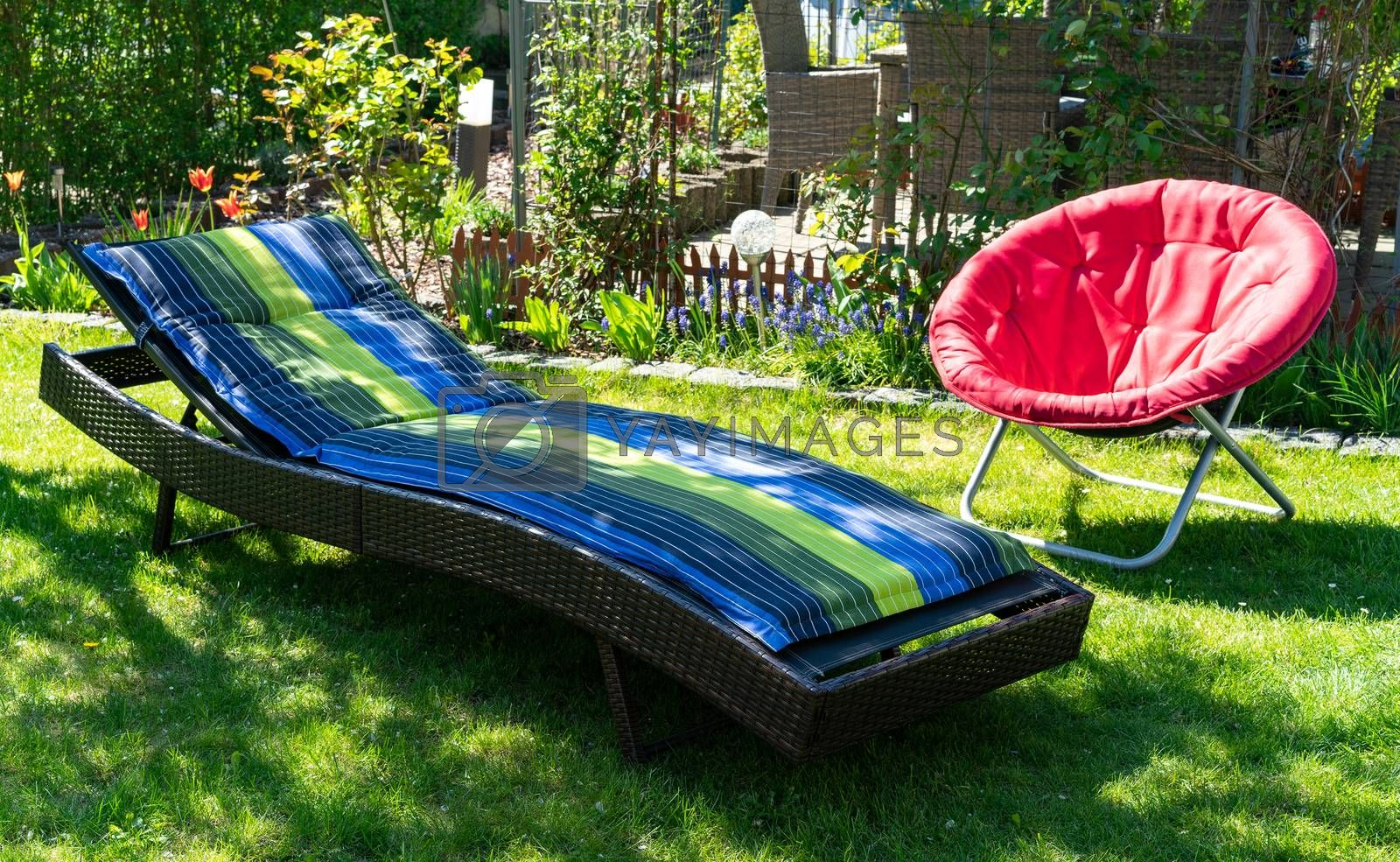 A blue and green colored sun lounger and a red round red folding moon chair in a green garden standing in the sun during spring time..