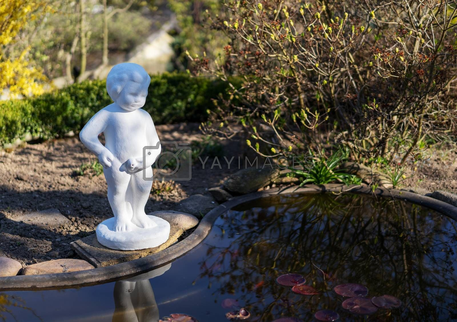 A sculpture in front of a garden pond. by Daniel Albach