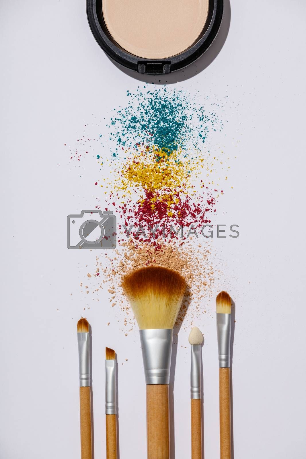 Makeup brushes and cosmetic products on a white background by klenova