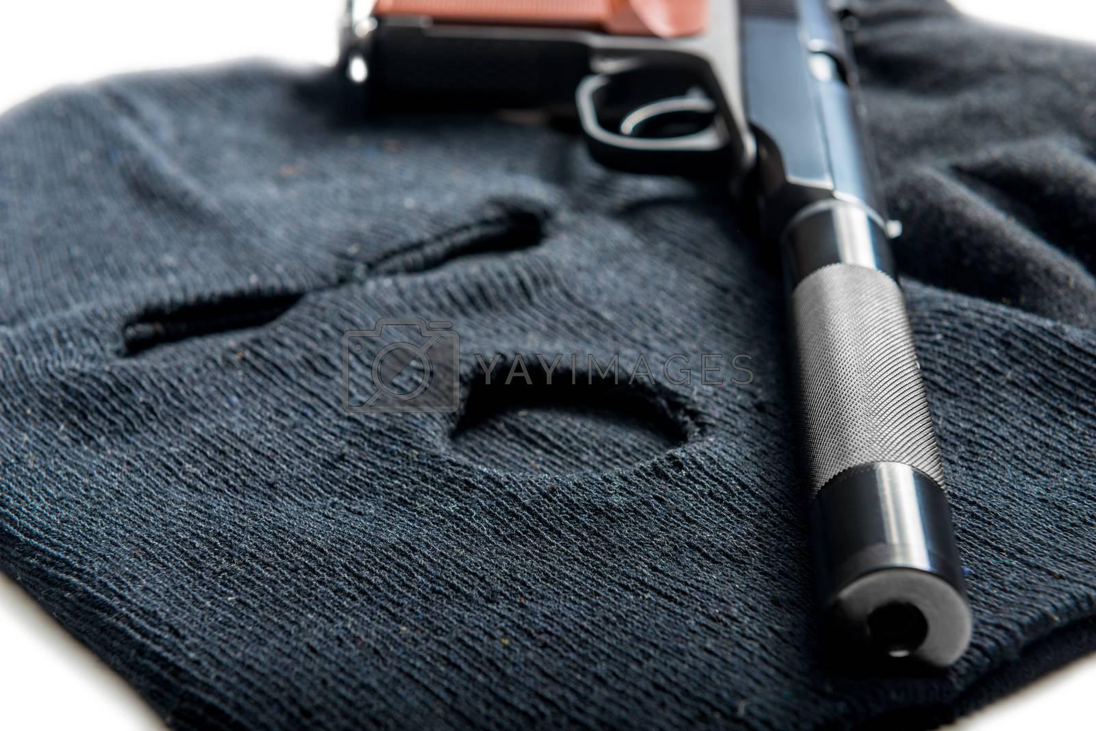 black mask balaclava and gun close up on a white table by Labunskiy K.