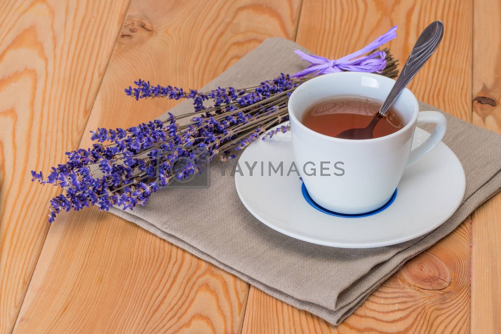 tea in a white cup and a bunch of dried lavender on a linen napk by Labunskiy K.