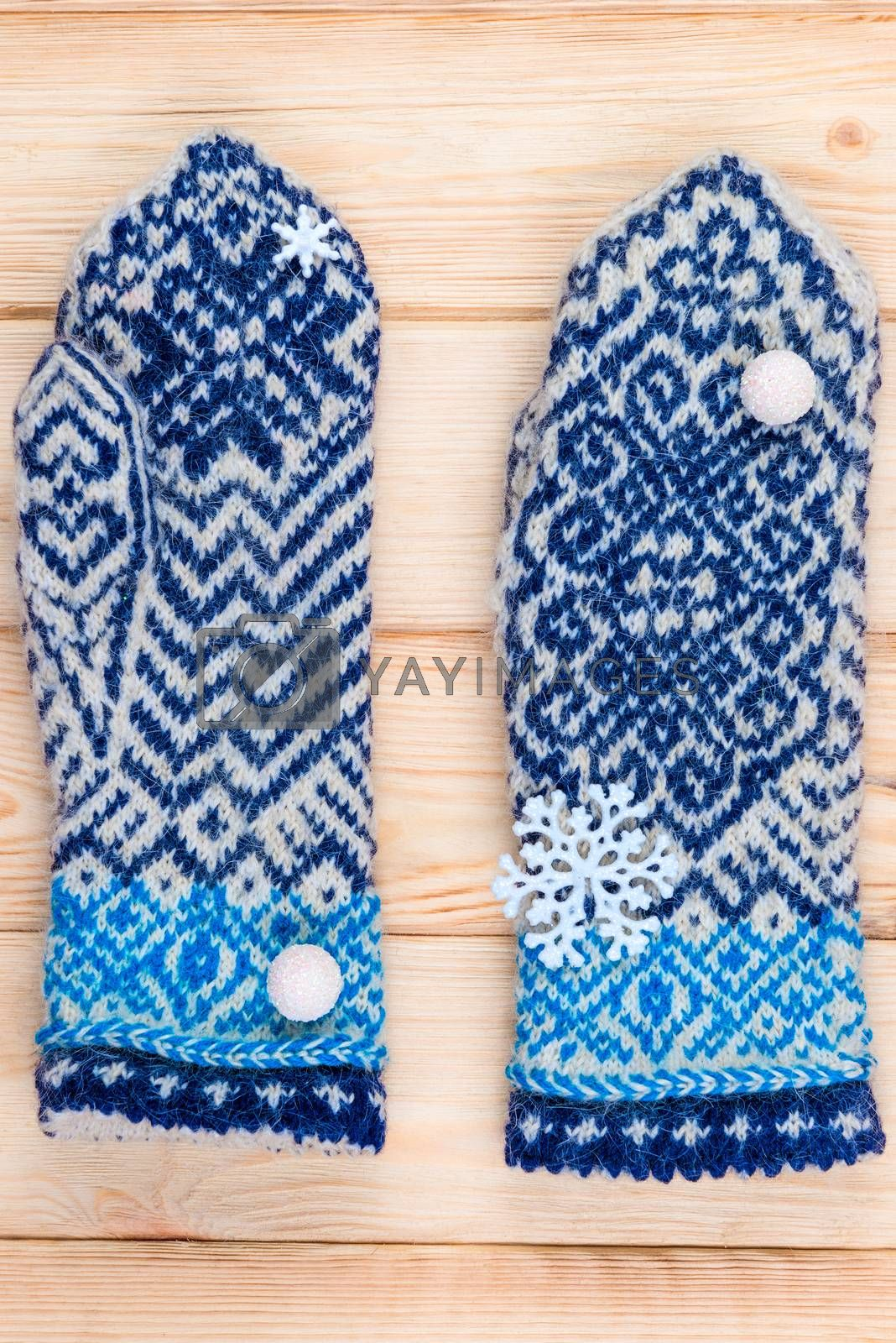 warm blue knitted mittens with winter pattern close up by Labunskiy K.