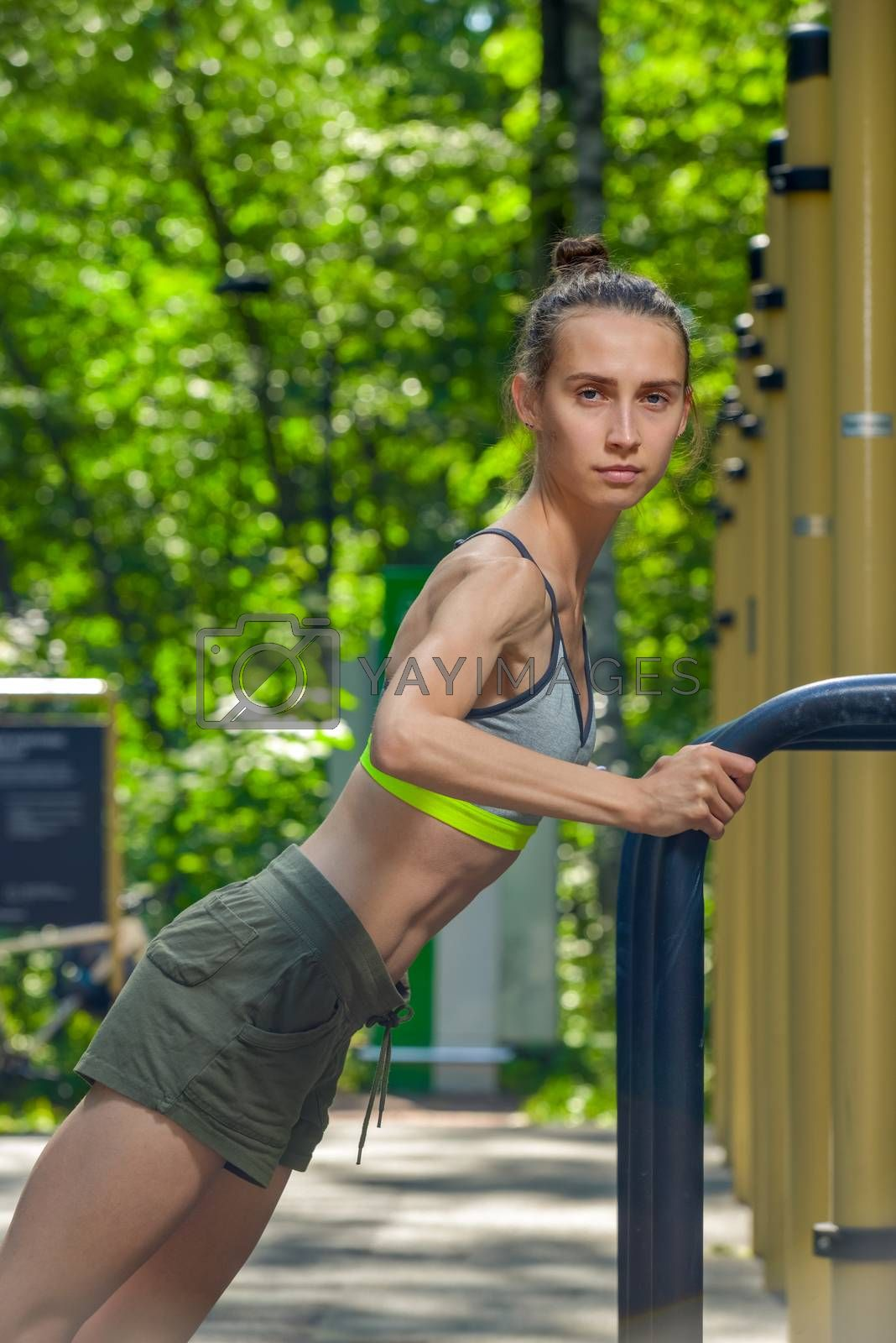 shooting sportswoman with a muscular figure on the sports field by Labunskiy K.
