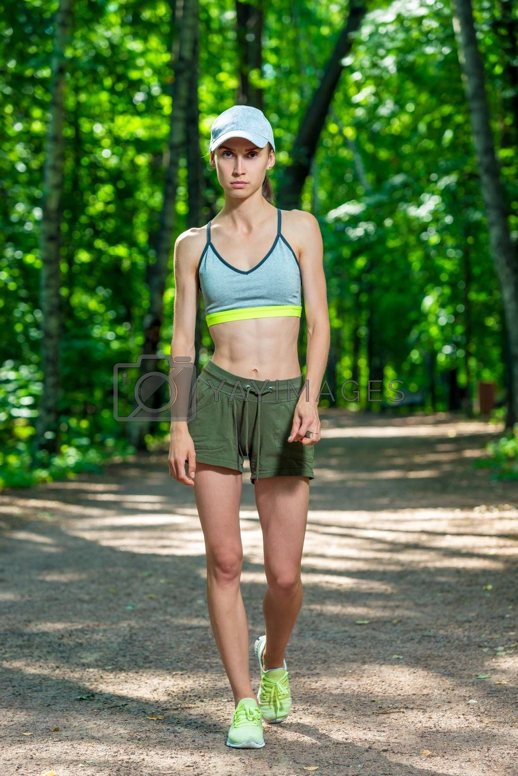 full length portrait of a female athlete in a summer park by Labunskiy K.