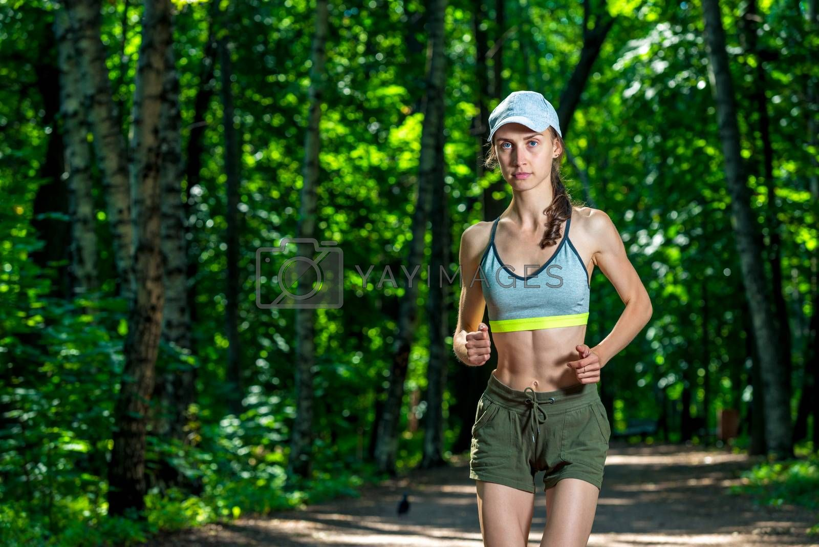 portrait of a beautiful muscular sportswoman while jogging in a  by Labunskiy K.