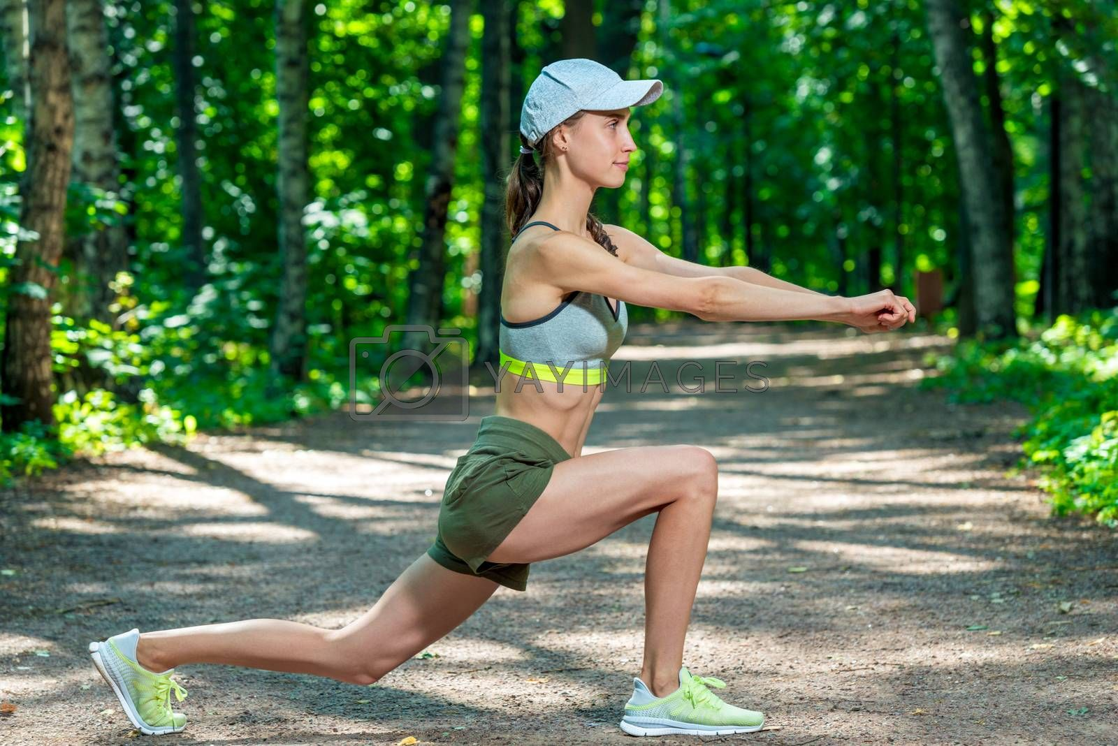 sporty woman performs stretching exercises in a summer park by Labunskiy K.