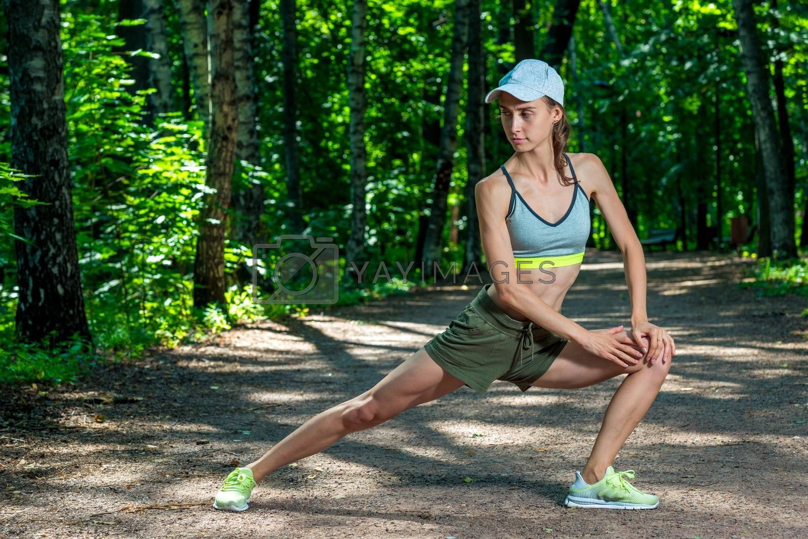slim girl with a sporty figure performs exercises in a summer pa by Labunskiy K.