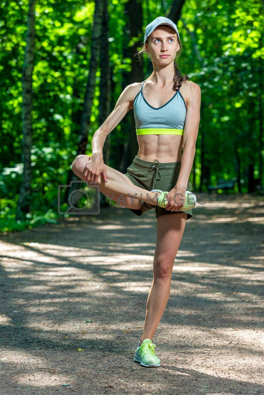 beautiful muscular athletic girl warms up her muscles before jog by Labunskiy K.