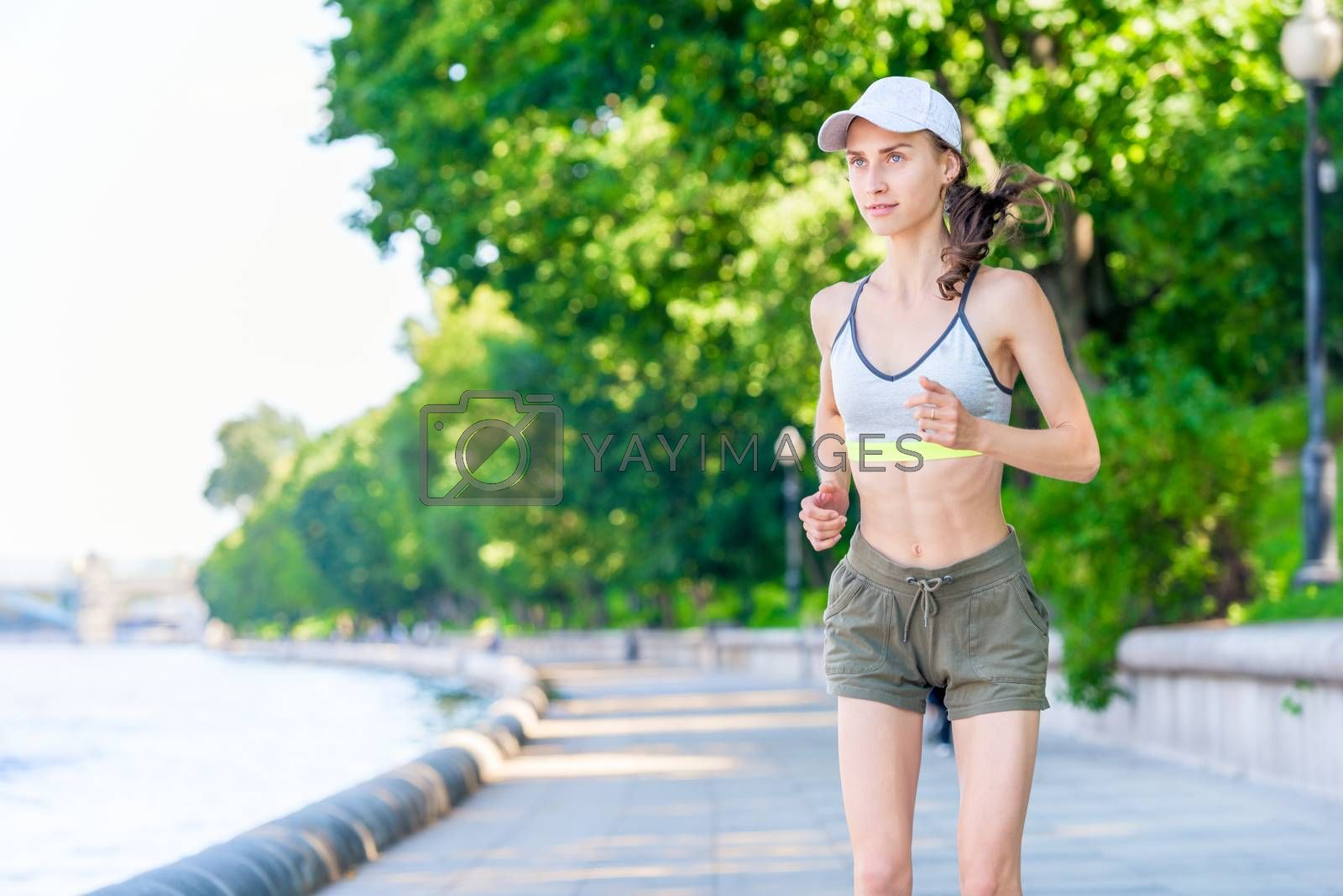 portrait of a running sports woman on the embankment in a city p by Labunskiy K.