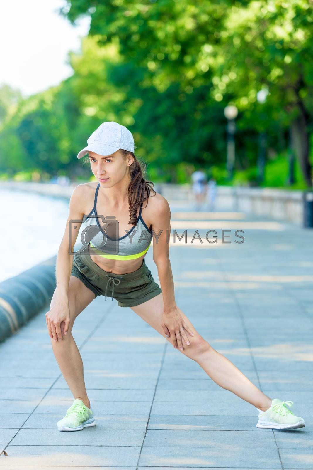 woman in sportswear with a muscular figure is warming up on the  by Labunskiy K.