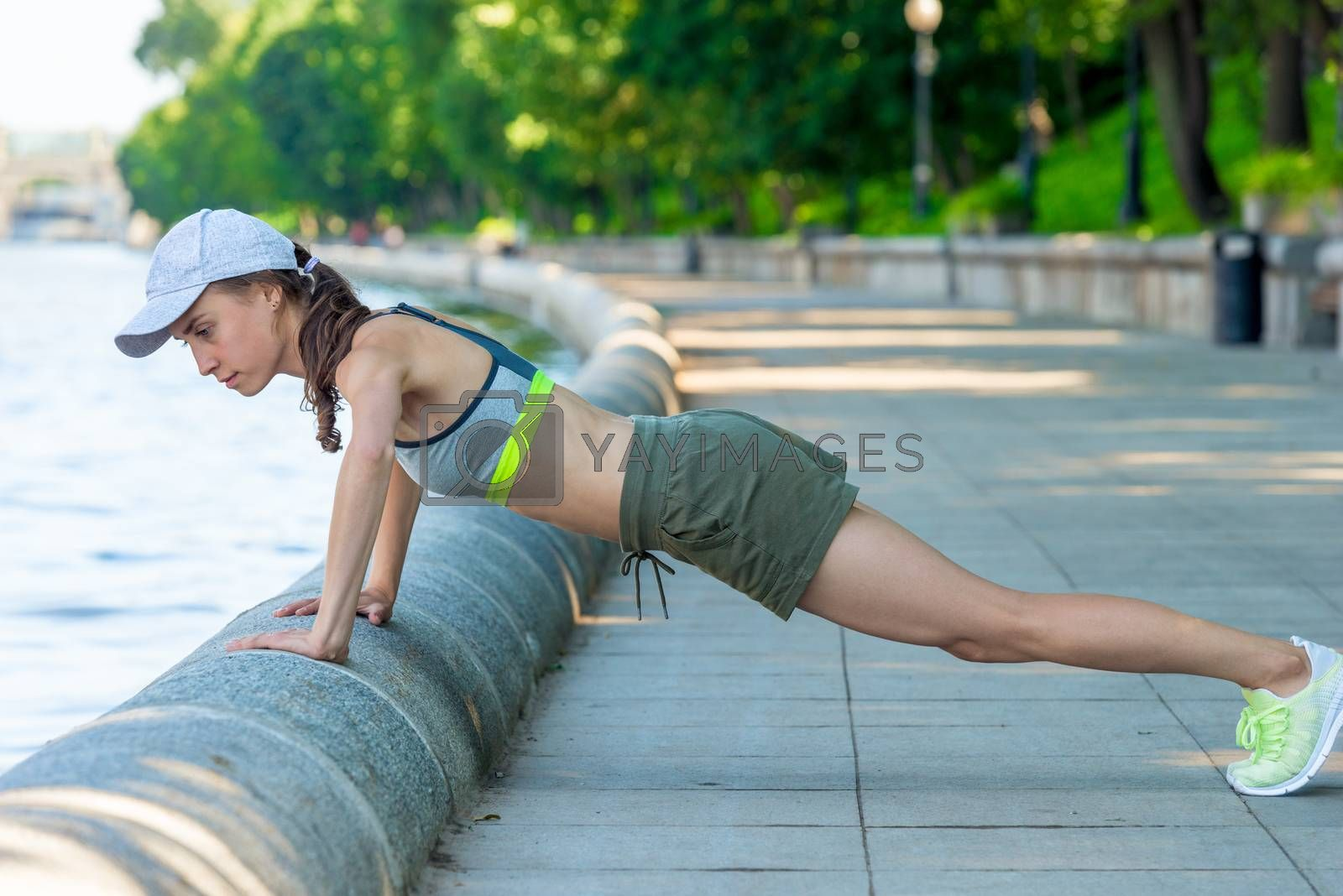 push-ups on the city promenade, active woman with a sports figur by Labunskiy K.