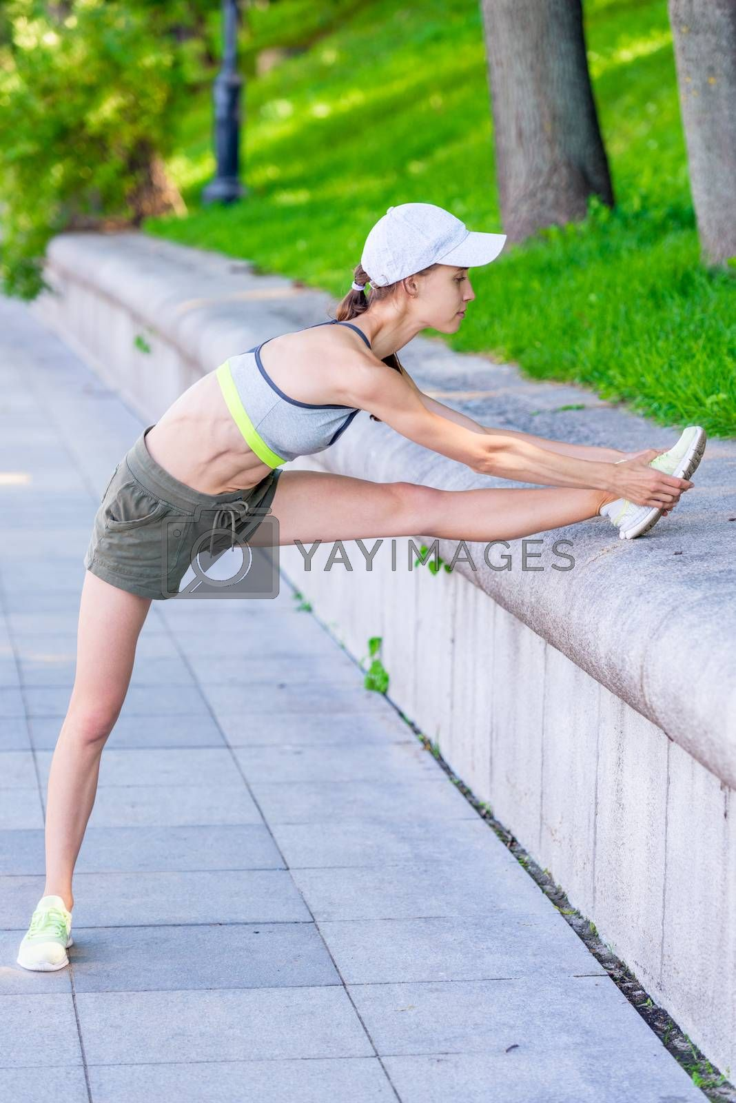 exercises on the city embankment, a female athlete stretches and by Labunskiy K.
