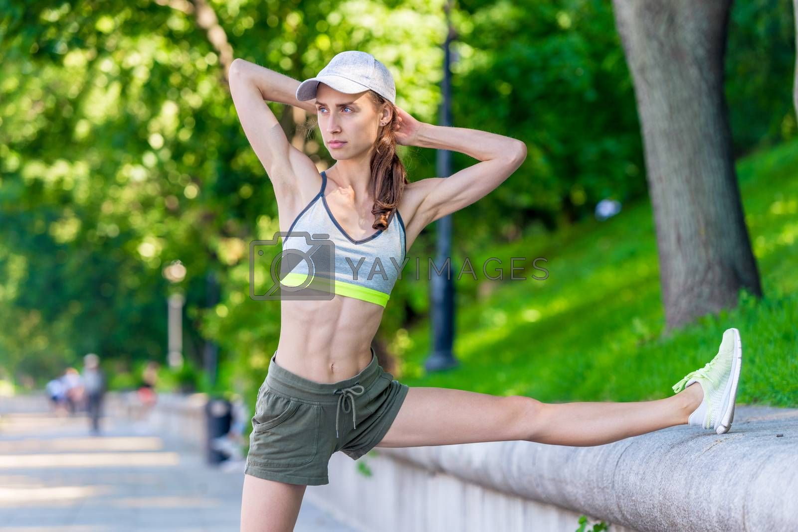 slender athletic woman warming up before jogging in a city park by Labunskiy K.