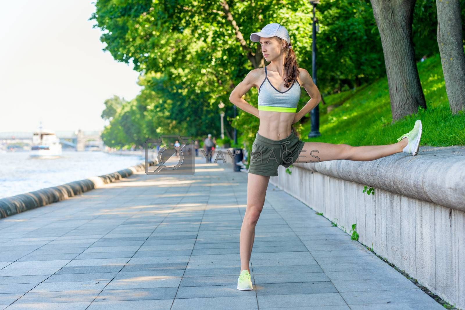 sporty woman warming up before jogging in a city park, portrait  by Labunskiy K.
