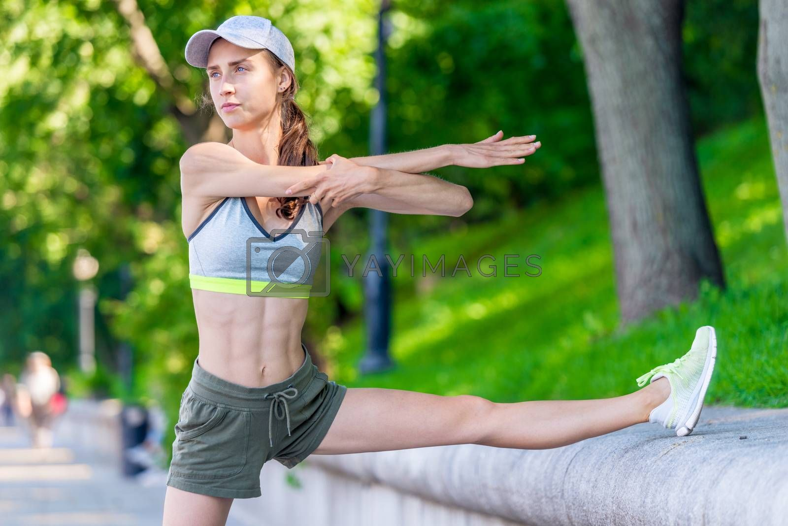 woman athlete warming up before jogging in a city park, portrait by Labunskiy K.