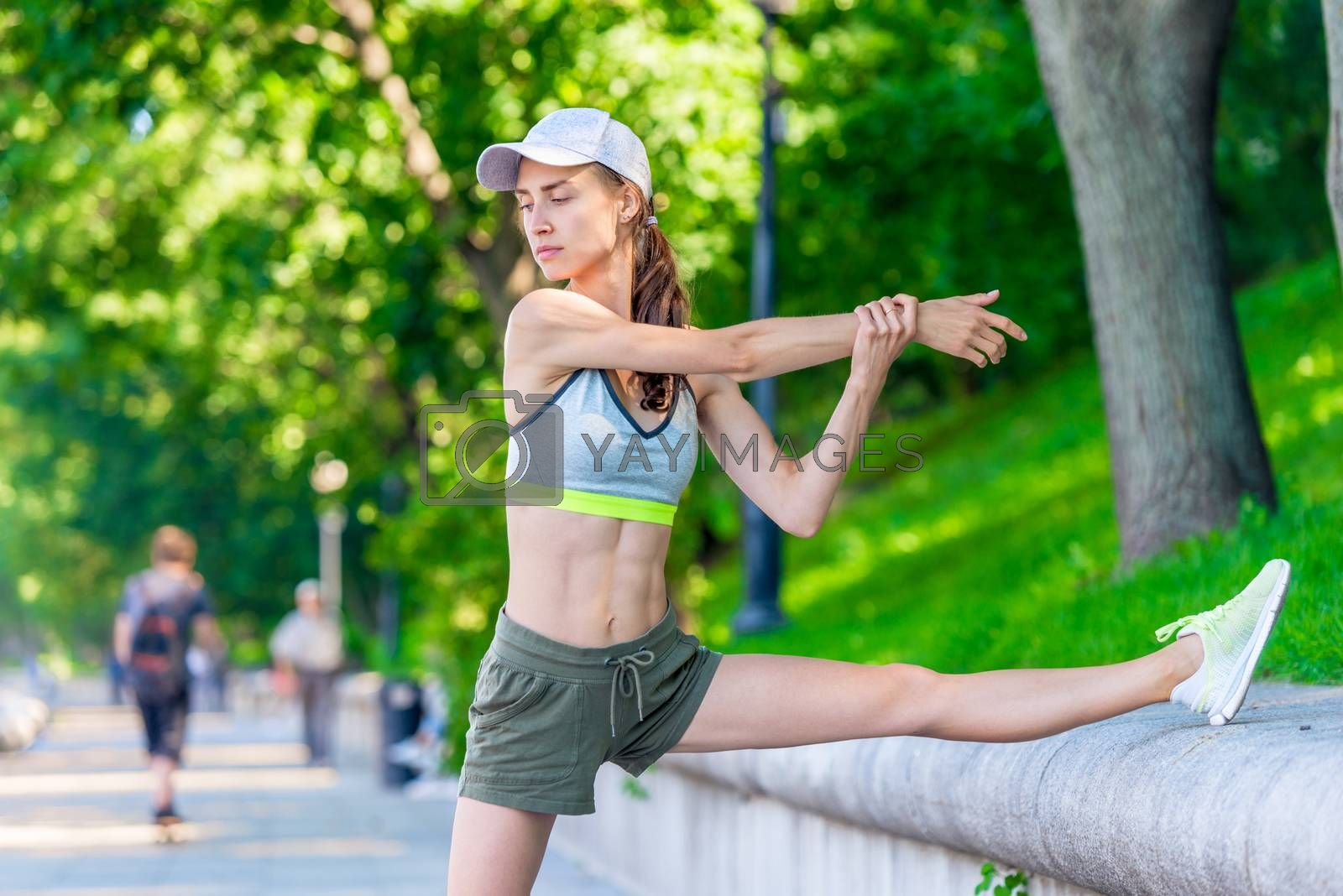 slender woman athlete warming up before jogging in a city park,  by Labunskiy K.