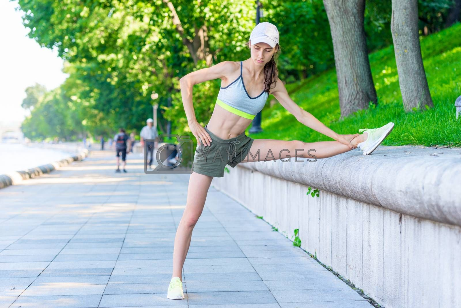 portrait of slender woman athlete who is warming up before joggi by Labunskiy K.