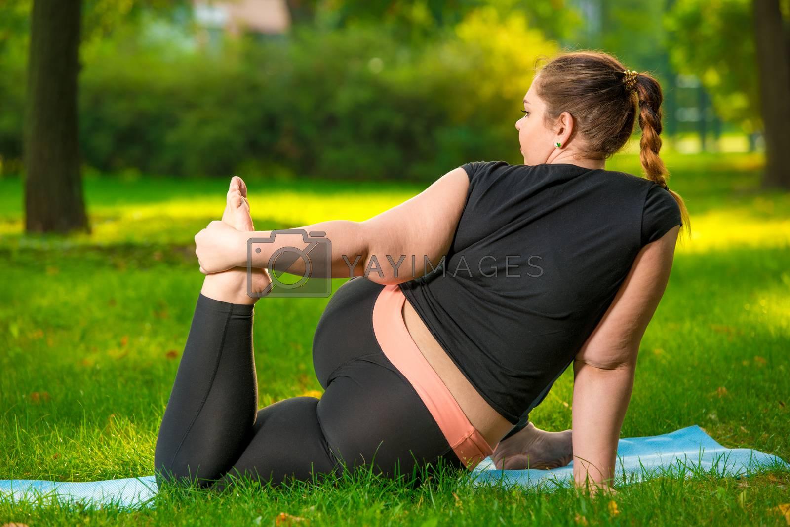fat woman in the park doing yoga, plus size woman is very flexib by Labunskiy K.