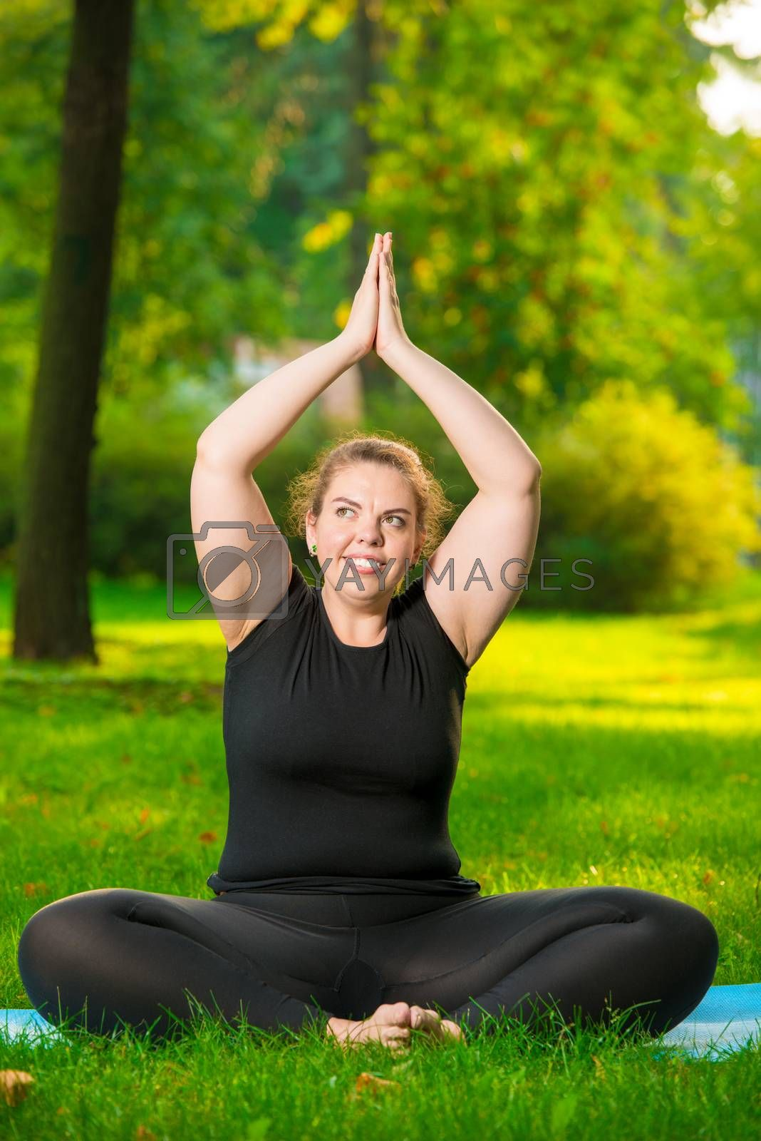 fat woman doing yoga in the park in the lotus position by Labunskiy K.