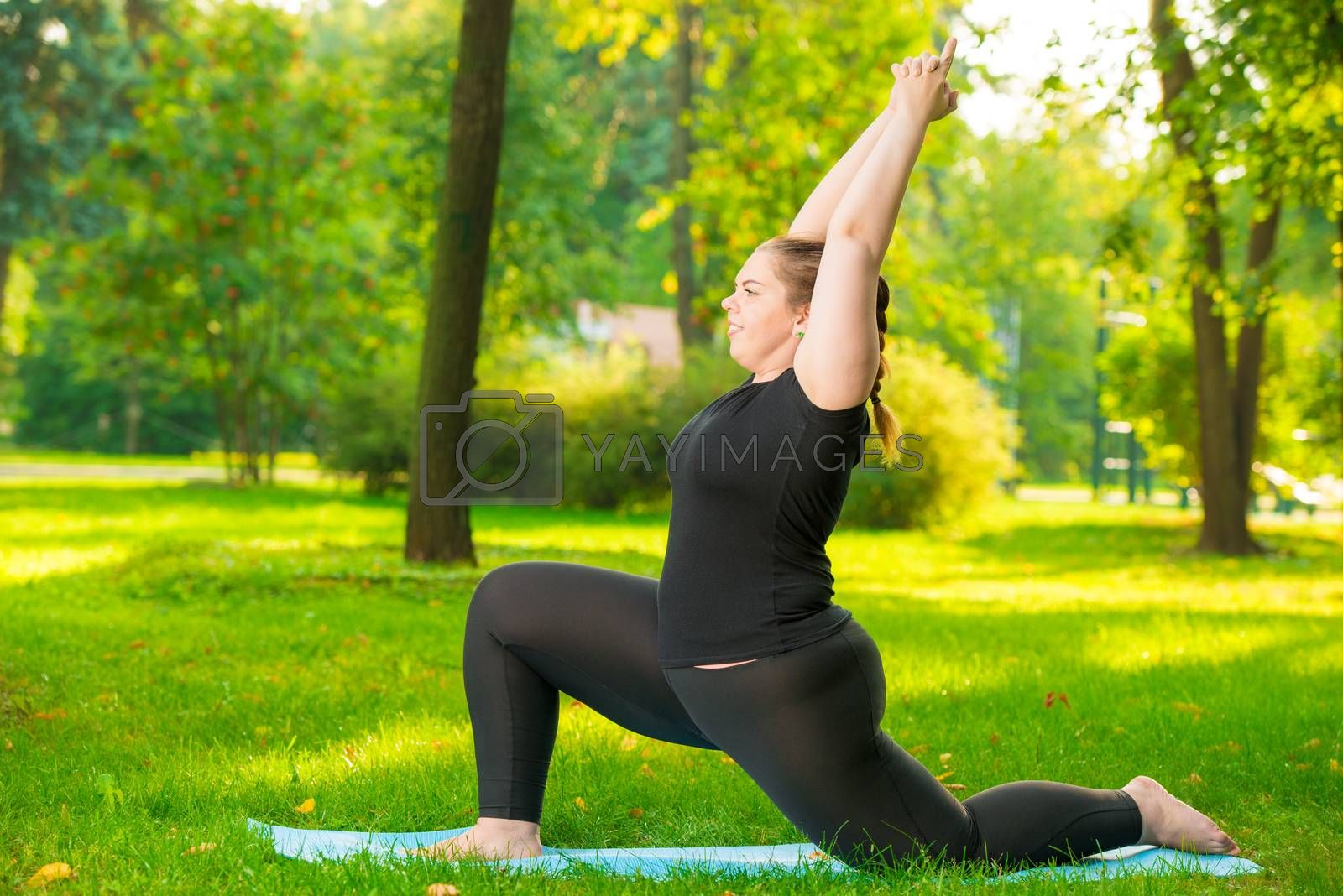 girl in the park is engaged in his figure, yoga exercises in the by Labunskiy K.