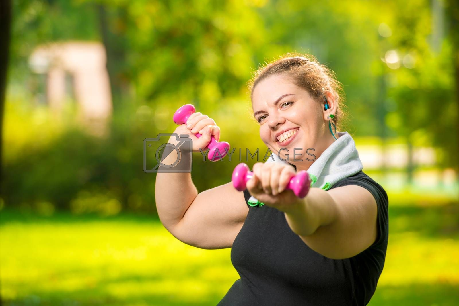 portrait of smiling plus size woman with dumbbells in the park d by Labunskiy K.