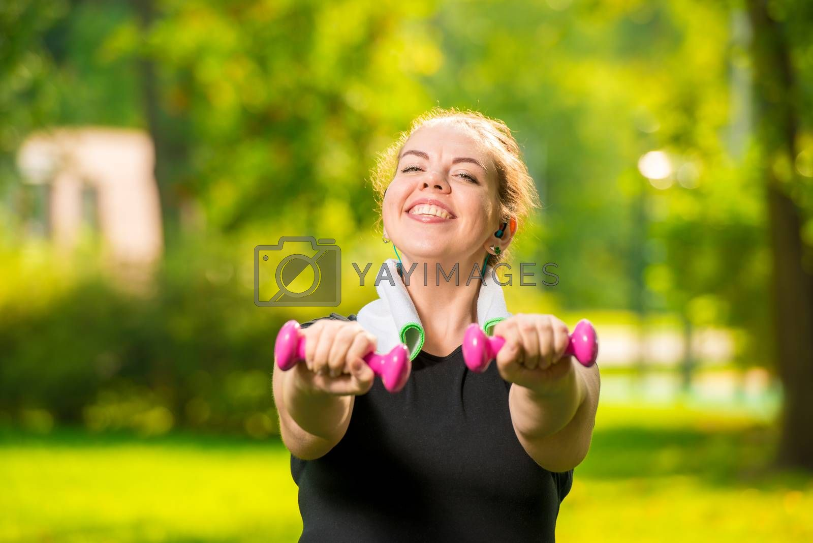 horizontal portrait of a smiling plus size woman with dumbbells  by Labunskiy K.