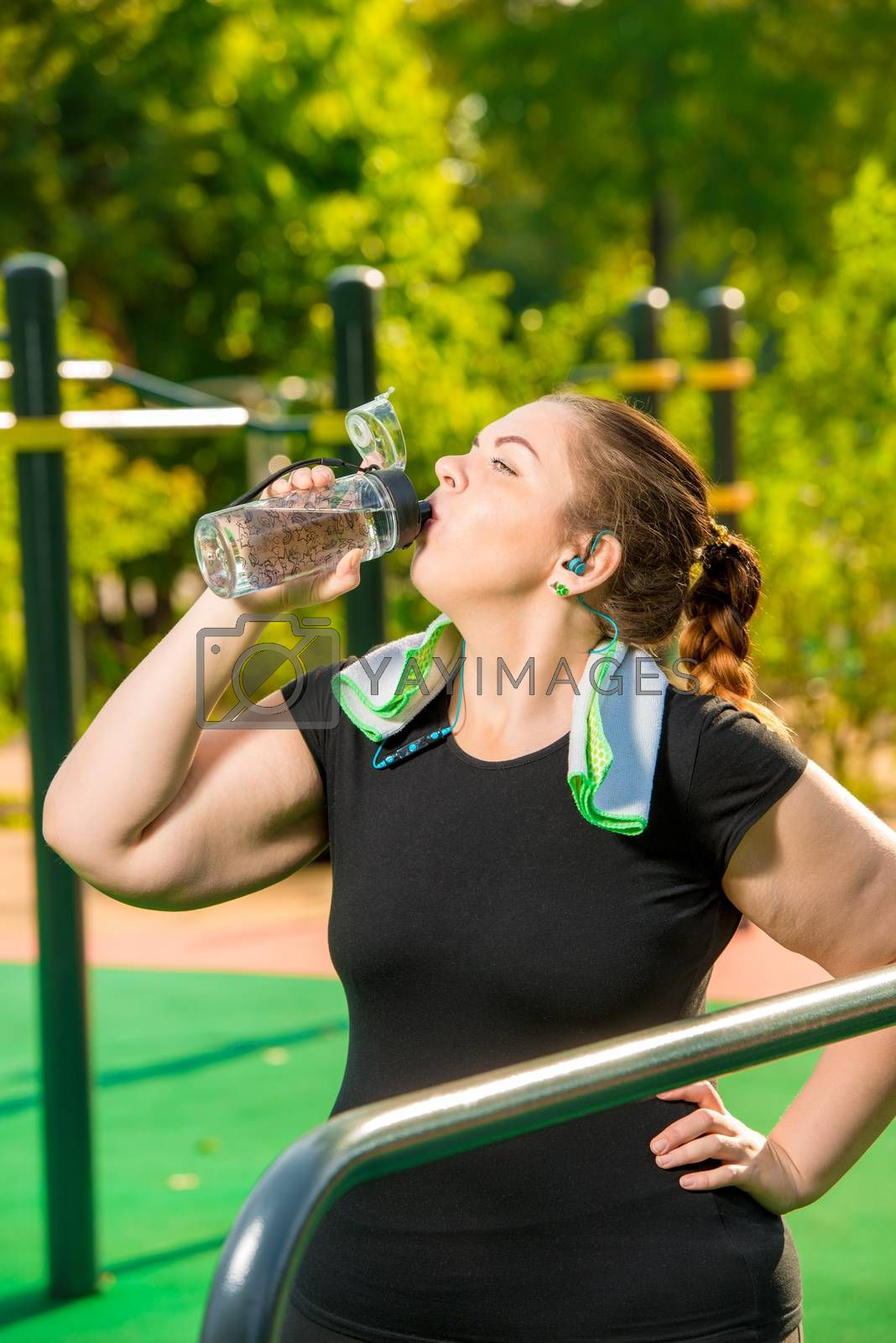 plus size girl drinks clean water from a bottle after sports act by Labunskiy K.