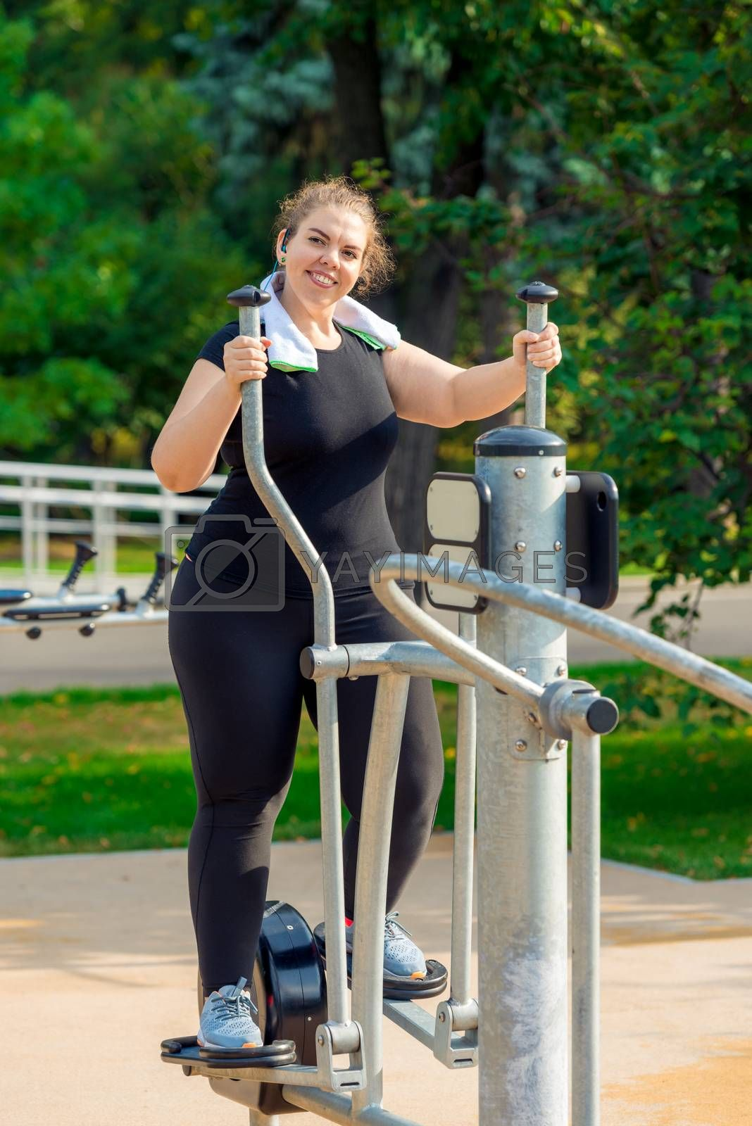 portrait of a young active fat woman engaged on a stepper simula by Labunskiy K.