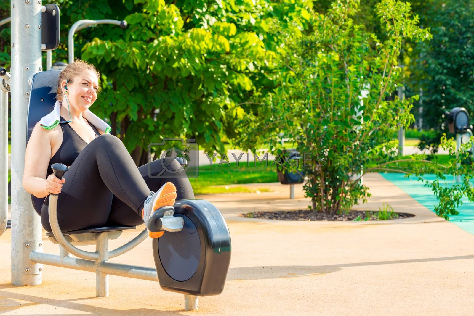 active oversized woman doing exercise on a stationary bike in a  by Labunskiy K.