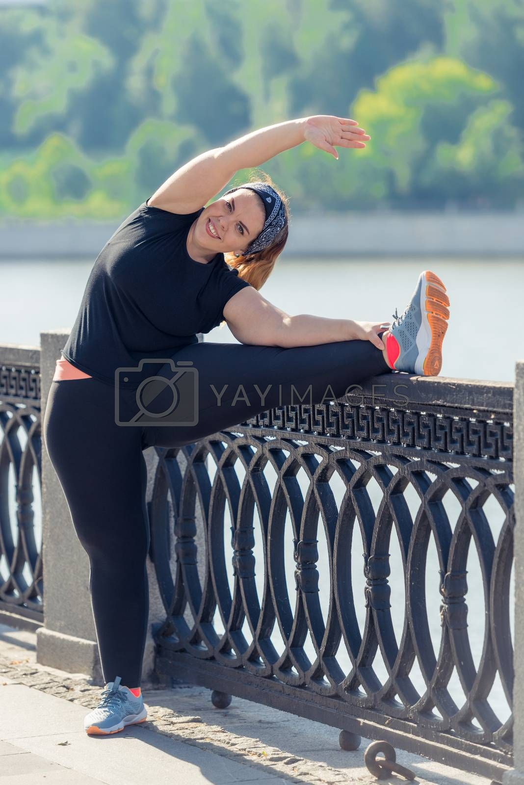 very flexible stout woman performs exercises on the embankment i by Labunskiy K.