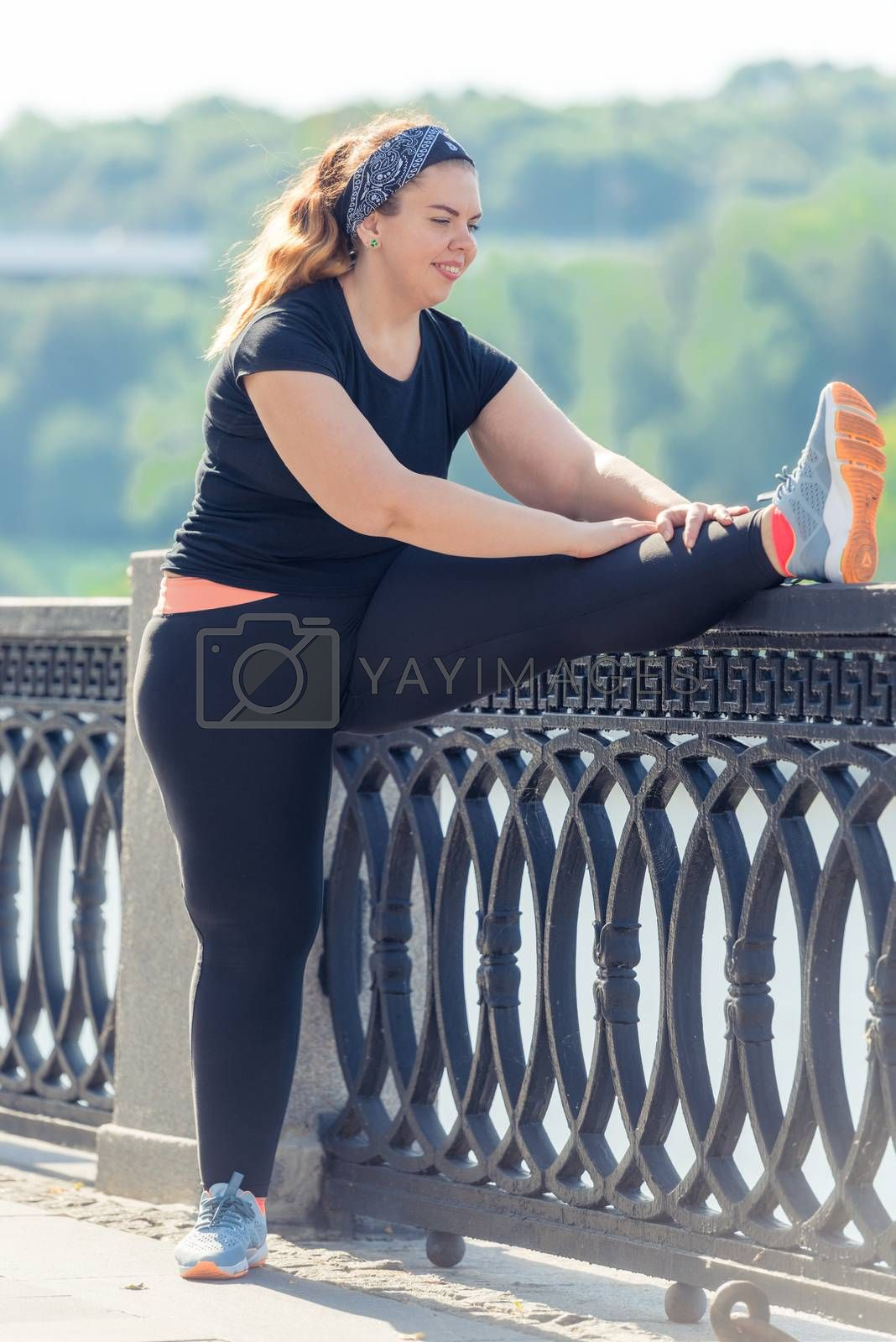fat woman performs exercises on the embankment in the city park  by Labunskiy K.