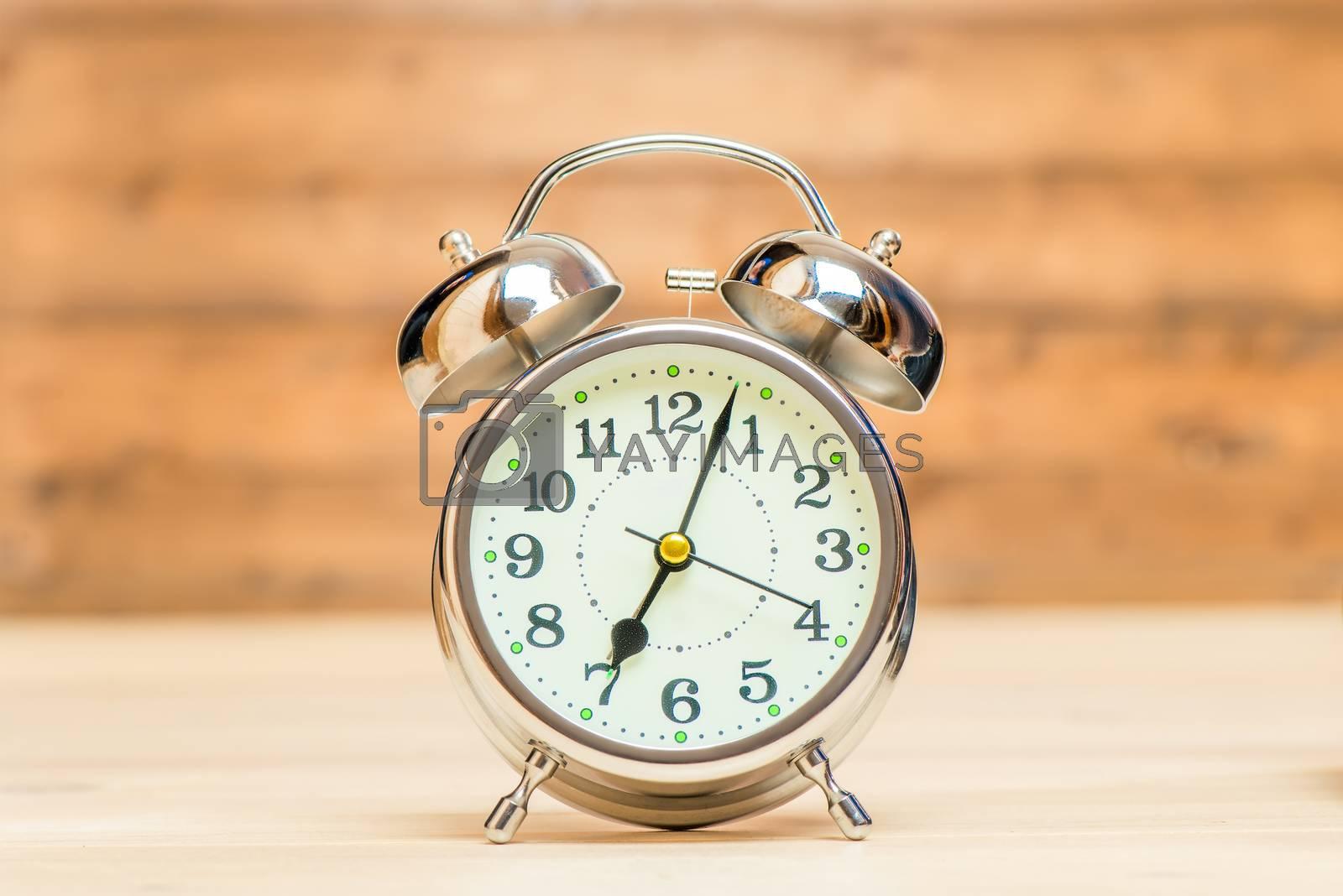 Silver alarm clock in retro style on a wooden background close-u by Labunskiy K.