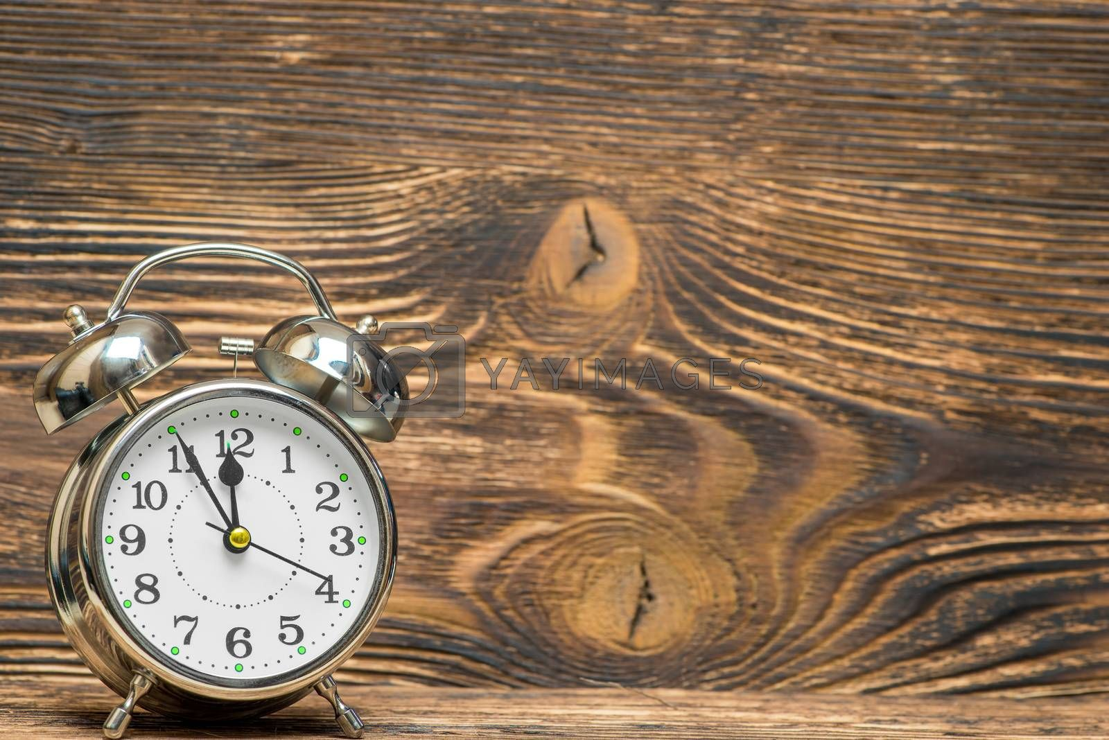 Retro alarm clock on a wooden background shows 12 hours, the spa by Labunskiy K.