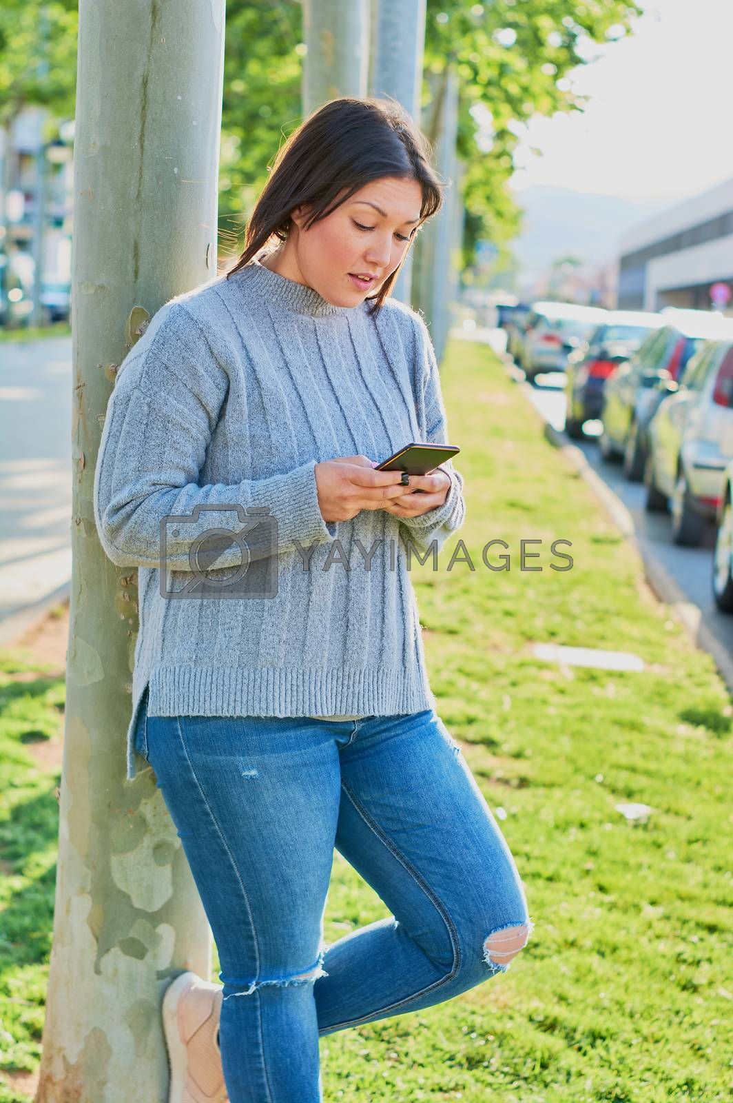 young girl talking on smartphone and typing messages with smartphone