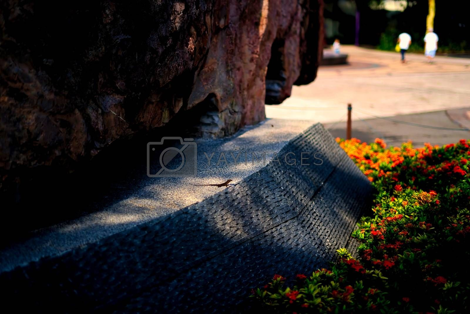 lizard reptile hidden on a pedestal between a sculpted rock and flowers with two blurry passerby in the background