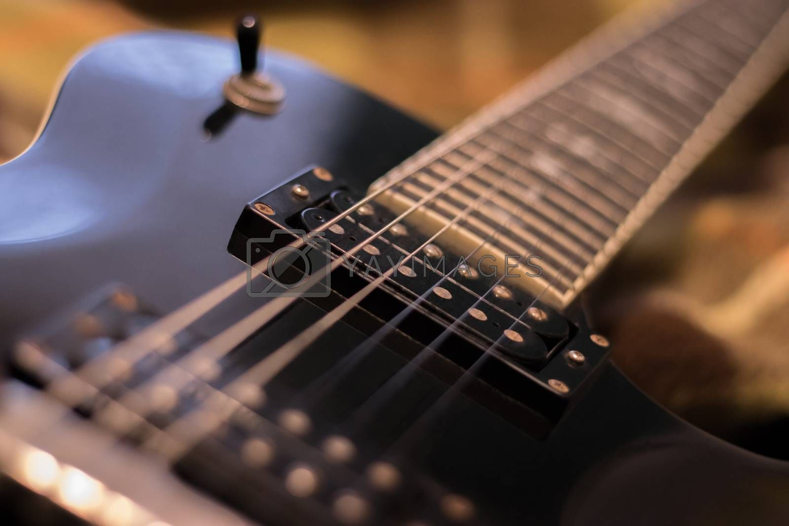 Fragment of the black electric guitar deck, pickup, neck and strings. Warm tones