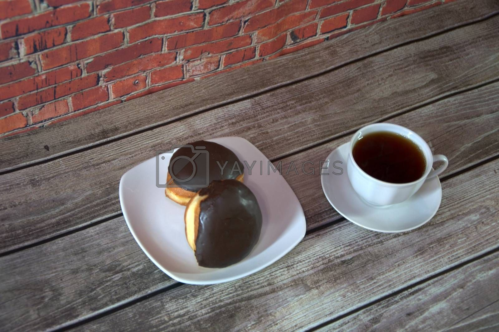 A cup of black tea on a saucer and a plate with two donuts in chocolate icing lie on a wooden table against a brick wall. Close-up. by Alex Yellow